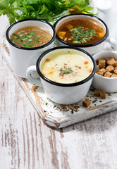 assortment of hot soups in mugs on wooden background, vertical top view