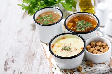 assortment of hot soups in mugs on wooden background