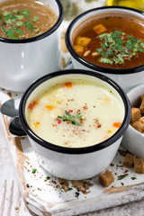 assortment of hot soups in mugs, vertical top view