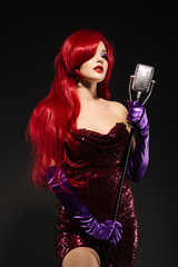 Young redhead woman with very long hair in red gown with microphone on the stand on a black background.