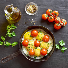 Fried eggs with tomatoes in frying pan