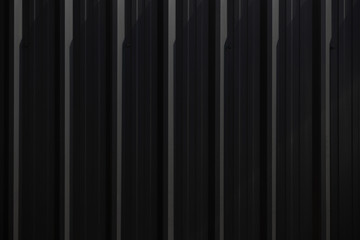 black corrugate wall background and texture,vertical black metal fence panel with light and shadow.