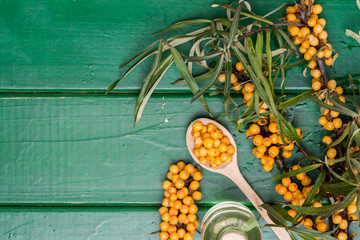 Sea-buckthorn oil and berries buckthorn branch in bowl on a wooden background. selective focus image