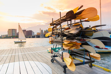 stand with paddles on a wooden pier by the river. sailing boat at sunset. Blurred background, copy space for your text