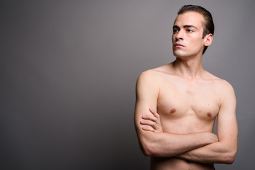 Young handsome man shirtless with arms crossed thinking