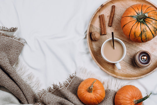 Cozy flatlay with wooden tray, cup of coffee or cocoa, candle, pumpkins on white sheets and blankets