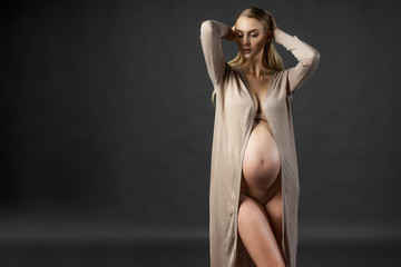 Beautiful pregnant young woman, wearing a lingerie and knitted dress, undone and open at her naked tummy touches her hair with her hands. Gray background. Fashion, pregnancy.