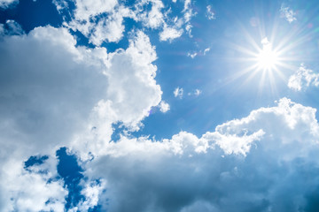 Blue sky background with clouds and sun.
