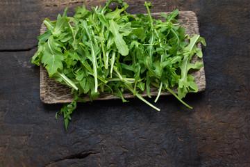 Fresh arugula salad,washed baby rocket on a wooden chopping board, breakfast healthy food.