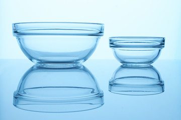 Two transparent bowls. Close up. Reflective surface.