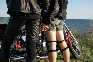 young couple holding hands on the background of a motorcycle. Family of bikers on the background of the bike and the sea