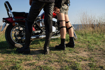young bikers in love in leather clothes and leather rough shoes stand holding hands near the bike