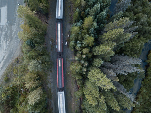 Aerial drone shot of Canadian country side with road, rail, train and creek
