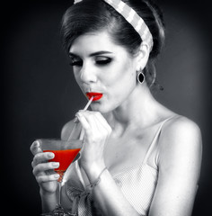 Pin up girl drink bloody Mary cocktail. Pin-up retro female style. Black and white photo with red color lips accent. Memories of youth on gradation grey background.