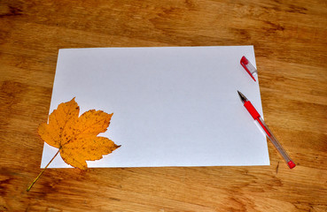 Maple leaf, white sheet of paper with pen on wooden table. Autumn season write letters and send postcards to relatives and friends in faraway countries