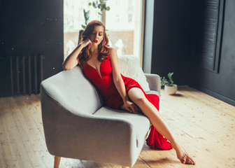 hot young woman, dressed in a long scarlet red long dress, sexually shows her bare legs sitting on a grey sofa in a loft modern room with window to the floor. Jessica rabbit halloween image