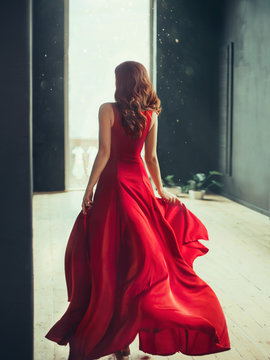 slim girl with red hair runs into a fashionable room in a loft style with dark black walls and window to the floor, dressed in a long flying dress in scarlet red color, art processing photo with no