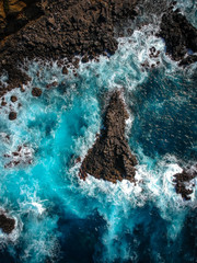 Aerial top view of sea waves hitting black volcanic rocks on the coastline with turquoise sea water. Amazing rock cliff seascape in the Portuguese coastline. Azores islands. Drone shot.