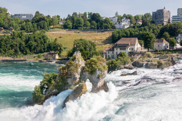 The Rhine Falls is the largest waterfall in Europe in Schaffhausen, Switzerland. Summer day with sun. View from castle Laufen