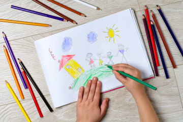 The child draws his family on a piece of paper with colored pencils. What can a children's picture tell. The concept of child psychology.