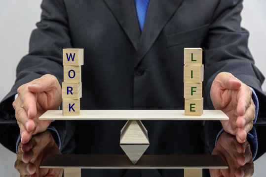 Work life balance concept : Businessman uses his hand protects 2 words on a seesaw or basic balance scale, depicts the balancing between time allocated for work and other aspect of life e.g family etc