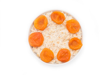 Oatmeal with dried apricots in white bowl on white bakcground. Isolated on white. Healthy food