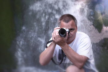 Male Photographer looking at you through camera. Waterfall backg