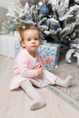 Beautiful cute little girl sitting on the floor near the New Year tree. Holiday mood, childlike spontaneity and sweet atmosphere