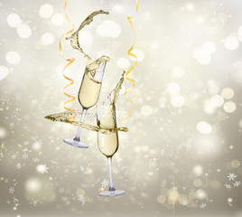 Two festive champagne glasses with splashes on silver bokeh background with lights