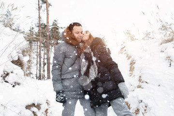 A young couple, a man and a woman are walking in a winter snow-covered forest. Winter leisure. Travel together. Love will warm in any frost