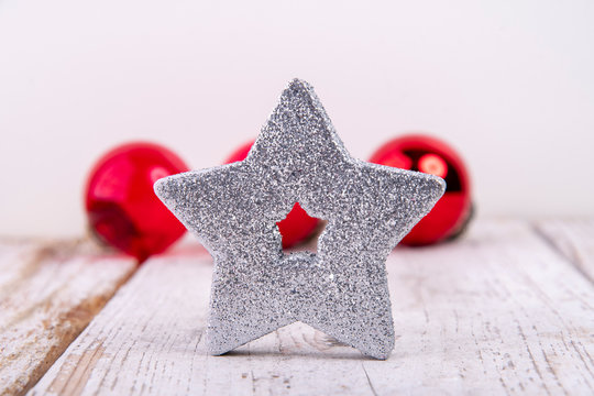 silver star with red christmas balls in the back on rustic old white wood