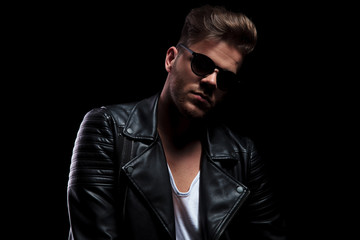 portrait of sexy man wearing black leather jacket and sunglasses