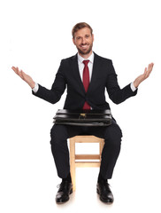 happy businessman sitting on chair and making welcoming gesture