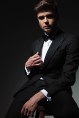 seductive man in black tuxedo sitting and holding collar