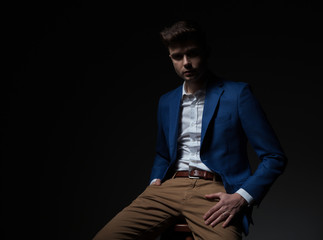 handsome smart casual man in blue suit sits on chair