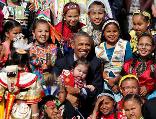 U.S. President Obama holds a baby as he poses with children at Cannon Ball Flag Day Celebration in Standing Rock Sioux Reservation in North Dakota