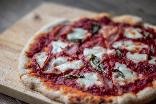 Delicious Italian pizza on a cutting board on dark background