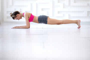 Woman exercising - doing a plank in a studio.