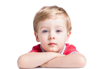Portrait of adorable little boy looking to the camera, isolated on white background