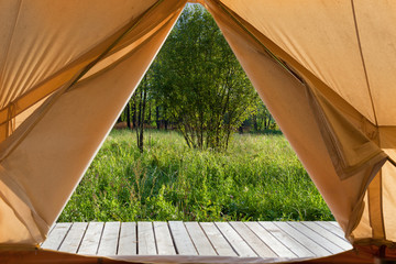 View from the canvas tent upon the green meadow