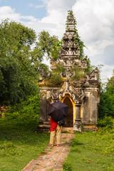 A woman under black sun umbrella is watching an ancient Buddhist pagoda, Myanmar.