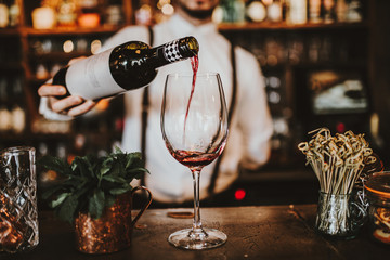 Close up shot of a bartender pouring red wine into a glass. Hospitality, beverage and wine concept.