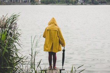 cold fresh morning foggy weather, autumn season, person back to camera in yellow rain coat and black umbrella in right hand on small wooden pier near river