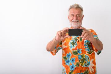 Studio shot of happy senior bearded tourist man smiling while ta