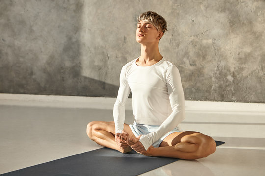 Flexible professional yoga instructor in long sleeved t-shirt and shorts sitting barefooted on mat, doing baddha konasana pose, closing eyes and breathing, having calm peaceful facial expression