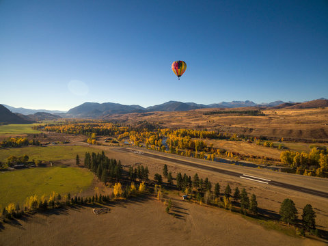 Hot Air Balloon Descends for a Landing. A hot air balloon comes to the end of it's flight in Winthrop, Washington, USA. It's autumn and the trees are changing color in eastern Washington, USA.