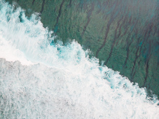 Aerial shot of the braking wave at the ocean reef.