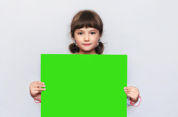 The little girl is holding a blank sheet of paper. Ukrainian patriots. Education. Advertising. Copy space, chroma key.