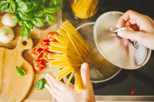 Man holding spoon with steaming pasta