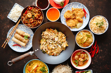 Asian food set. Noodles, fried rice with chicken, tom yum soup, spring rolls, deep fried fish and udon with prawns. Top view on dark rustic background. Oriental style food concept composition.